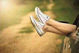 Bild zeigt Beine die aus einem Autofenster heraus taumeln