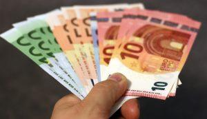 Das Bild zeigt eine Hand, die Euro-Scheine hinhält