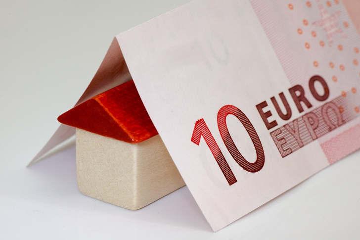 kredit fuer haus - 10 Euro schein liegt gefaltet über einem kleinen Holz-Häuschen Modell